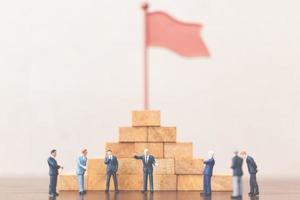 empresários em miniatura sobre um bloco de madeira, líder empresarial de sucesso e conceito de trabalho em equipe