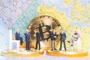 empresários em miniatura em uma pilha de moedas de criptomoeda com um mapa-múndi ao fundo, dinheiro e conceito de sucesso de negócios financeiros