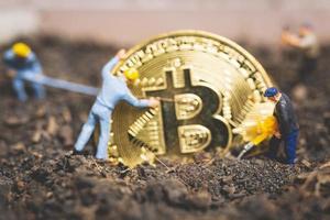 trabalhadores em miniatura cavando o chão para descobrir criptomoeda bitcoin brilhante, conceito de trabalho bem-sucedido