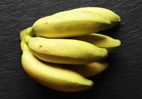 pequenas bananas amarelas em fundo preto foto