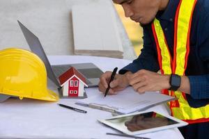 engenheiro trabalhando em tablet e laptop na construção do local foto