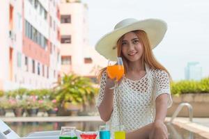 Mulher asiática com grande chapéu branco de verão sentada no banco da piscina, com um coquetel perto da piscina