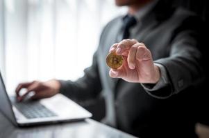 empresário mostrando moedas de ouro com símbolo de bitcoin