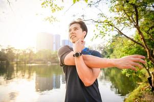 homem asiático esticando o ombro após terminar de correr