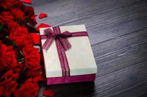 caixa de presente e rosa em fundo de madeira