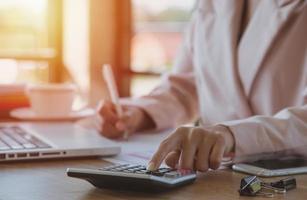 jovem empresária usando calculadora trabalhando em um laptop em sua estação de trabalho