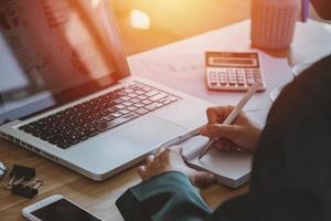 jovem empresária trabalhando em um laptop em sua estação de trabalho foto