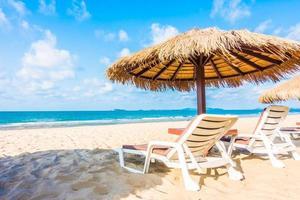 guarda-sol e cadeira na praia tropical foto