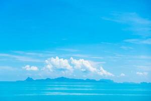 lindo oceano com nuvens no céu azul foto