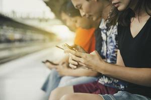 grupo de amigos usando smartphones em uma estação de trem