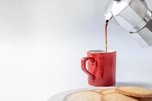 caneca de café vermelha com biscoitos no fundo branco foto
