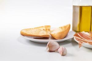 pão, alho e azeite no fundo branco foto