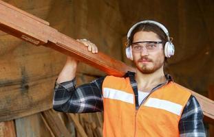 homem carregando madeira foto