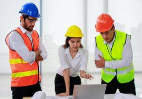 grupo de engenheiros olhando para um laptop foto
