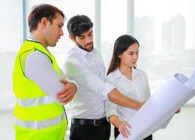 grupo de engenheiros olhando para um projeto foto