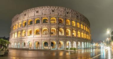 visão noturna chuvosa do coliseu em roma, itália