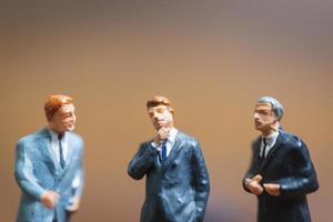 empresários em miniatura sobre um fundo de madeira, líder empresarial e conceito de trabalho em equipe