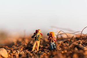 viajantes em miniatura com mochilas - conceito de montanhismo, caminhada e mochila ao ar livre foto