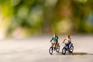 pessoas em miniatura andando de bicicleta ao ar livre com um fundo verde bokeh, conceito de esporte e viagem