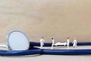 médicos em miniatura com enfermeiras carregando um paciente em uma maca, conceito de saúde