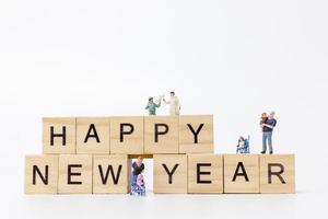 famílias em miniatura em blocos de madeira com o texto feliz ano novo em um fundo branco foto