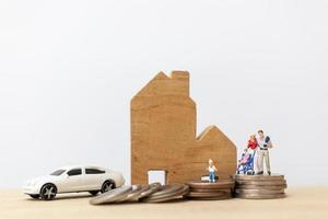pais e filhos em miniatura com uma casa e uma pilha de moedas, conceito de família feliz