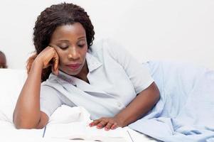 jovem lendo um livro na cama foto