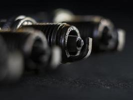um close-up das velas de ignição com defeito, contra um fundo preto foto