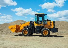 Carregador frontal preto-amarelo com rodas pequenas contra o fundo de uma grande pilha de areia de pedra