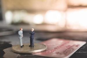 empresários em miniatura sobre um conceito de moeda, negócios e finanças