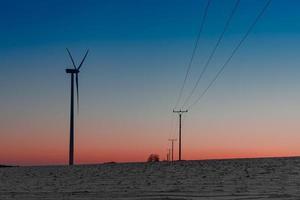 usina eólica no campo próximo a uma linha de energia ao pôr do sol
