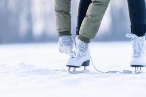 amarrando os cadarços de patins de inverno em um lago congelado, patinando no gelo foto