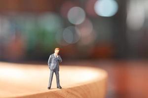 empresário em miniatura parado pensando em um fundo colorido