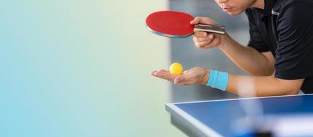 masculino jogando tênis de mesa com raquete e bola em um ginásio esportivo foto
