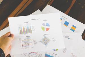 gráficos e tabelas financeiras em uma mesa de madeira