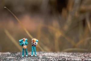 mochileiros em miniatura em um piso de concreto com um fundo de natureza bokeh