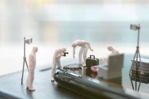 polícia em miniatura e detetives trabalhando em um smartphone, investigação de cena de crime e conceito de crime cibernético foto
