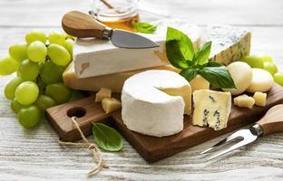 vários tipos de queijo em um fundo branco de madeira foto