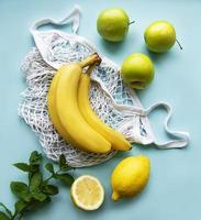 suculentas frutas cítricas maduras e bananas em uma sacola de compras ecológica