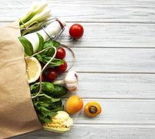 comida saudável em saco de papel, vegetais e frutas foto