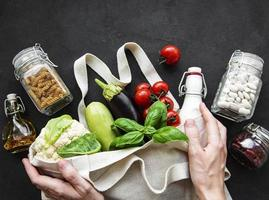 saco ecológico com frutas e vegetais, potes de vidro com feijão, macarrão