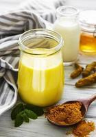 leite dourado com canela, cúrcuma, gengibre e mel sobre fundo branco de madeira