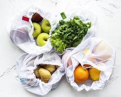 frutas e verduras de verão em bolsas reutilizáveis de malha ecologicamente corretas com fundo de mármore