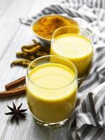 leite dourado com canela, açafrão, gengibre e mel sobre fundo de mármore branco