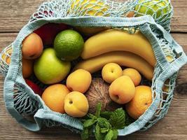 Saco de compras de malha com frutas orgânicas em fundo de madeira