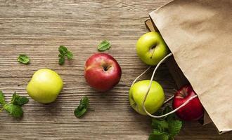 maçãs frescas em um saco de papel em um fundo de madeira