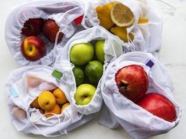 Malha sacolas de compras com frutas orgânicas em fundo de mármore