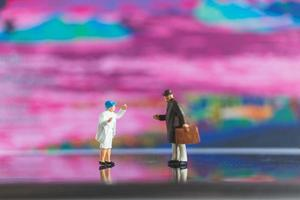 pessoas em miniatura dando um aperto de mão em um fundo colorido