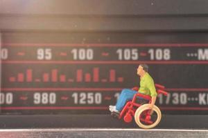 homem deficiente em miniatura sentado em uma cadeira de rodas sintonizando uma estação de rádio
