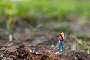 viajante em miniatura com uma mochila caminhando em um prado, conceito de viagem e aventura